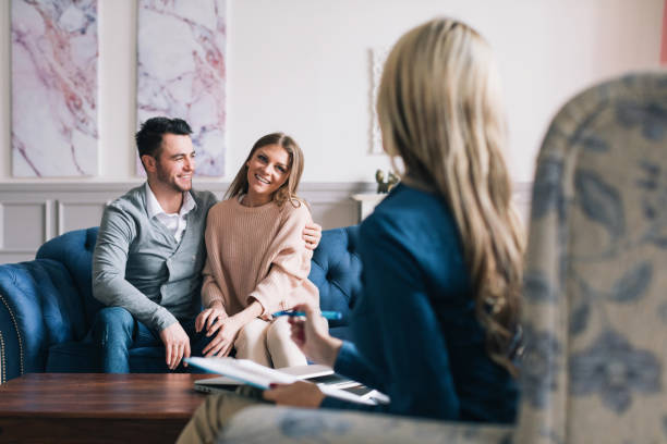 Beautiful and happy young couple visiting psychologist for relationship counselling. stock photo