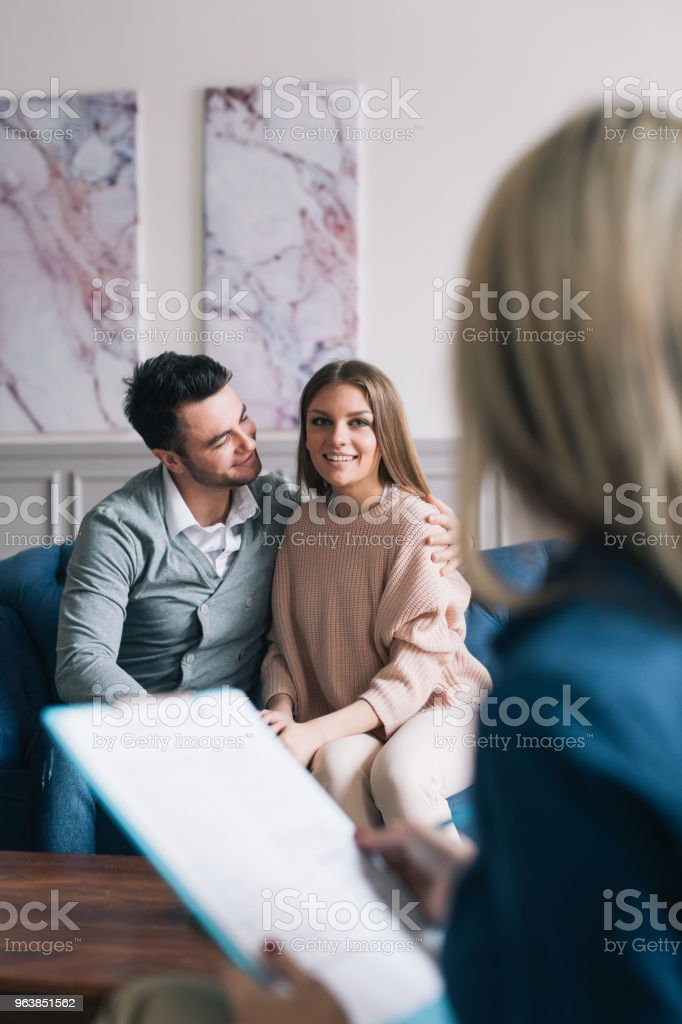 Beautiful and happy young couple visiting psychologist for relationship counselling. - Royalty-free Adult Stock Photo