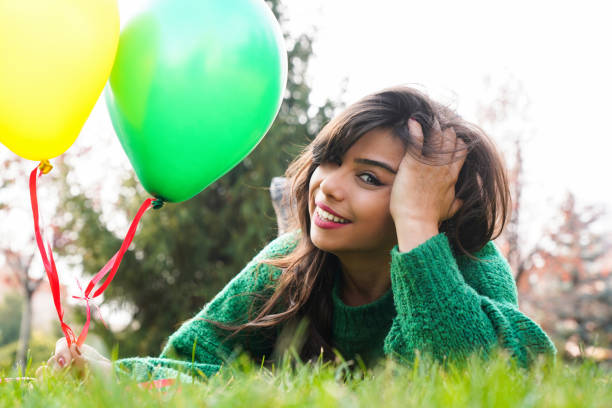 Beautiful and happy young woman lying on the grass smiling and balloons stock photo
