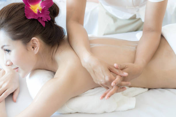 Beautiful and healthy young woman relaxing with back massage in spa salon stock photo