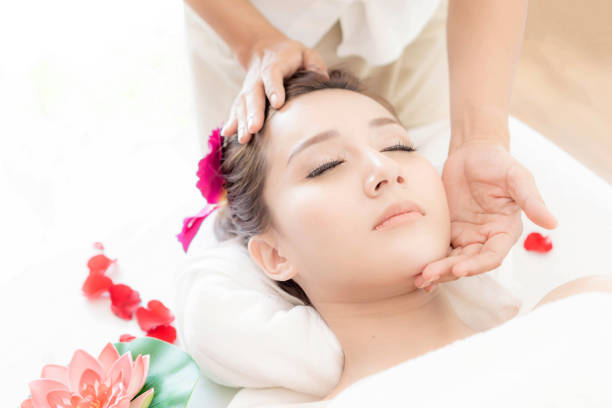 beautiful and healthy young woman relaxing with face massage  at beauty spa salon stock photo
