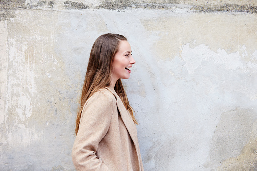 Beautiful and laughing woman in coat, profile