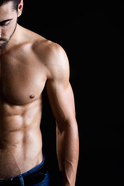bellissimo e muscolare uomo su sfondo scuro. - a petto nudo foto e immagini stock