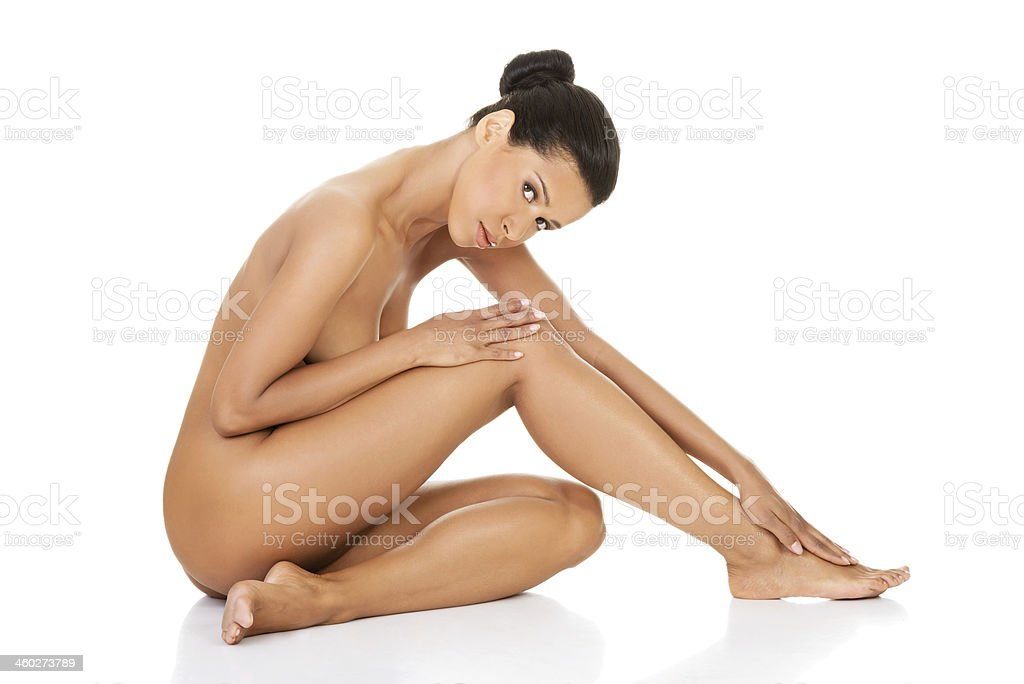 Beautiful and naked woman sitting. Side view. stock photo