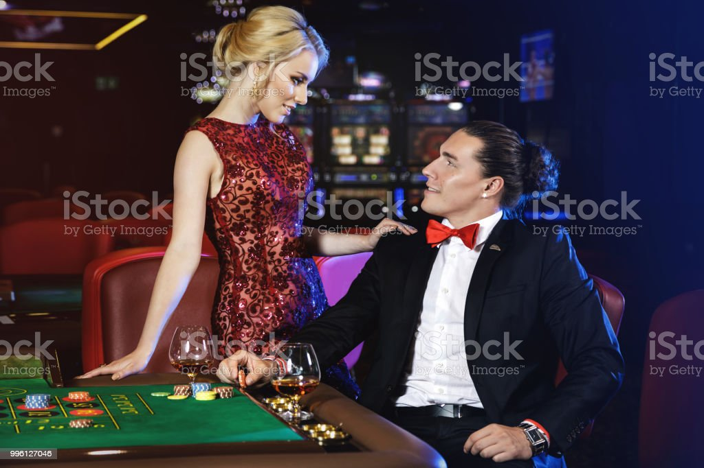 Beautiful And Rich Couple Playing Roulette In The Casino Stock Photo -  Download Image Now - iStock