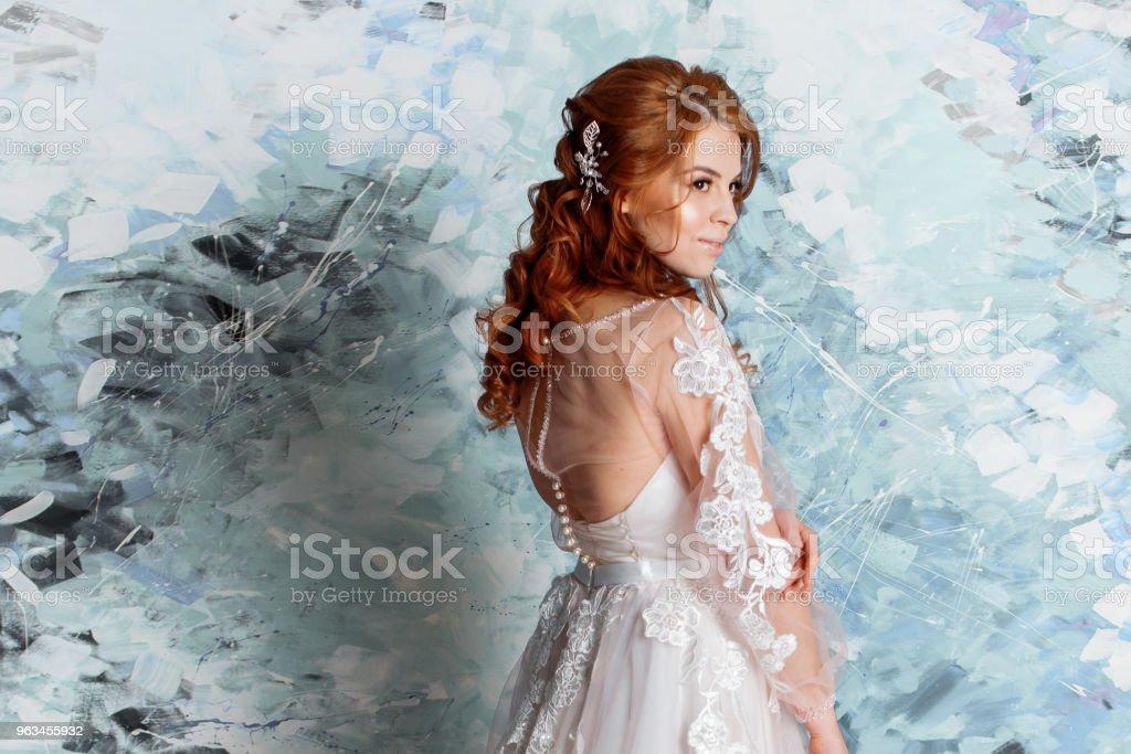 Piękna i romantyczna panna młoda w sukni ślubnej z długimi rękawami. Młoda rudowłosa kobieta w sukni ślubnej - Zbiór zdjęć royalty-free (Barwne tło)