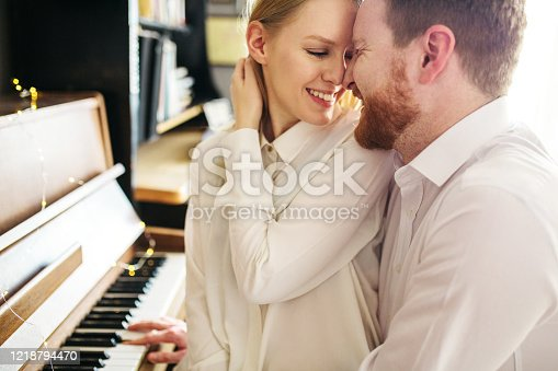 849355030 istock photo Beautiful and romantic couple sitting next to piano and embracing 1218794470