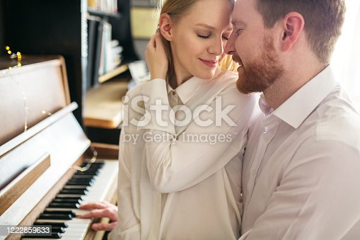 849355030 istock photo Beautiful and romantic couple sitting next to piano and embracing 1222859633