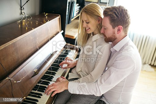 849355030 istock photo Beautiful and romantic couple sitting next to piano and embracing 1222859710