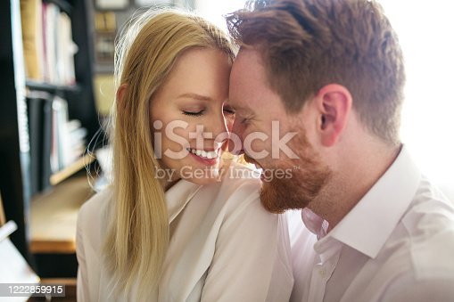 849355030 istock photo Beautiful and romantic couple sitting next to piano and embracing 1222859915