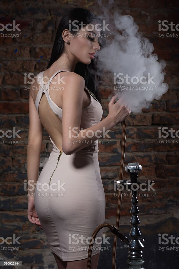 Beautiful and sexy glamorous woman smoking hookah stock photo