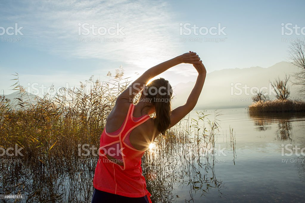 Beautiful and sporty young woman stretching after jogging outdoors stock photo