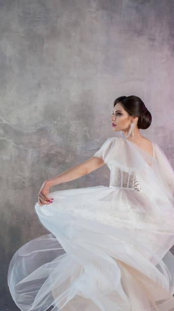 schöne und stilvolle braut im hochzeitskleid mit einem üppigen fliegenden rock in - hochzeitskleider online stock-fotos und bilder