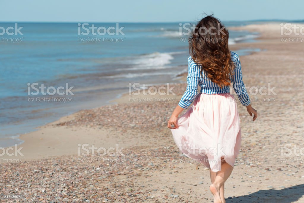 Beautiful and stylish brunette walking on the beach. Back view stock photo