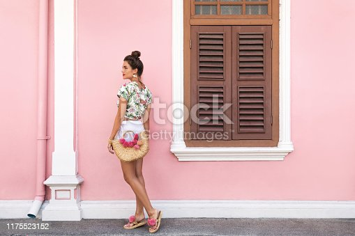 Beautiful and stylish woman wearing summer clothes is posing beside the house with a pink wall
