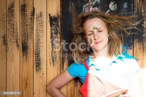 istock Beautiful and young girl stands on a wooden wall background which is painted with black paint. The girl's face is stained with green paint. Her hair evolves from the airflow. She smiles with soft lips. 1020481310