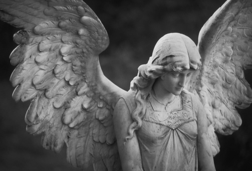 Beautiful Angel Statue stands watch over graves in a cemetery in the northeastern U.S. (Scanned black and white negative with noticeable grain).