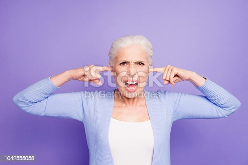 661896674istockphoto Beautiful angry gray-haired old lady wearing casual, closing her ears with fingers, yelling. Isolated over pastel violet purple background 1042555058