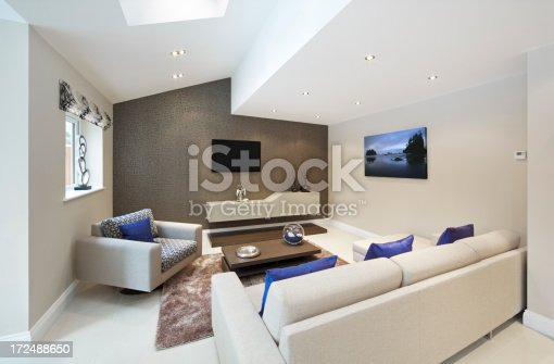 A beautiful TV room in a luxury new home with cream coloured furnishings and blue cushions  to add a dash of colour. Photographed to express the intriguing angularity of its architecture. On the back wall (feature wall with patterned wall covering) is a wall mounted storage unit and above it a flat LCD TV screen. Copyright for the artwork on the wall is owned by the photographer.Looking for a Living Room image Then please see my other Living Room and related images by clicking on the Lightbox link below...
