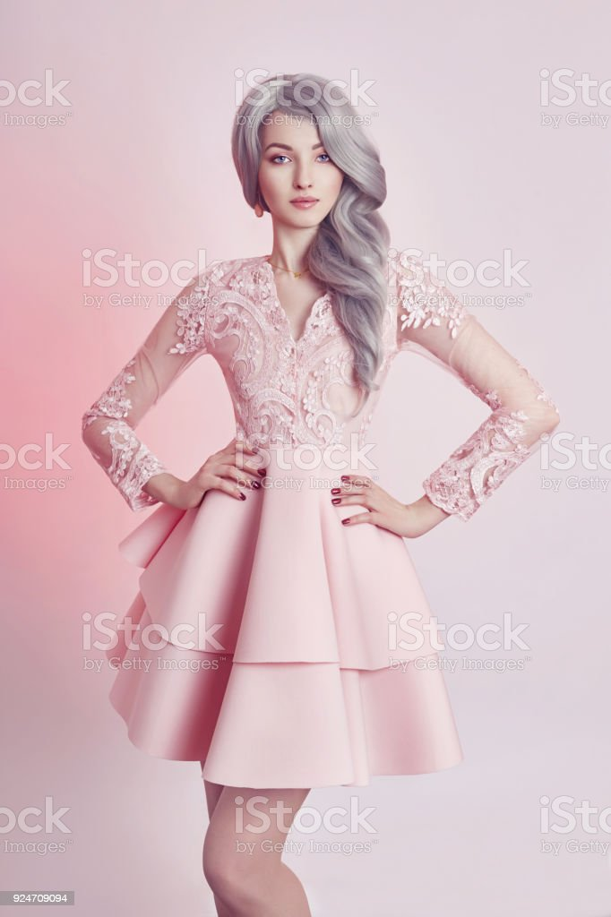 Beautiful anime doll girl in pink dress on pink background. A girl with long blonde ash hair. Fabulous look of woman anime heroine stock photo