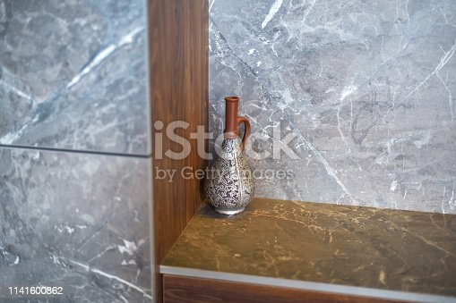 istock A beautiful antique jug , a vase stands in the corner of the room on a marble table. 1141600862