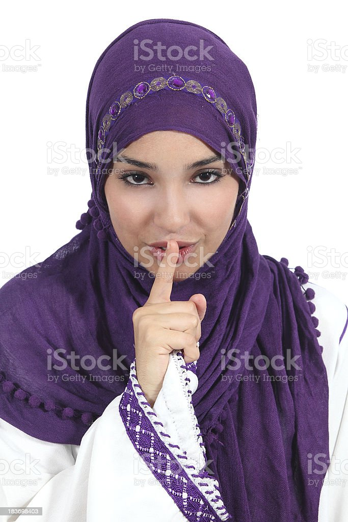 Beautiful arab woman asking for silence with finger on lips stock photo