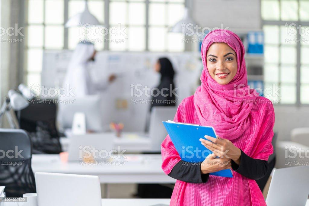 Beautiful arab woman at work, holding documents, looking at camera.