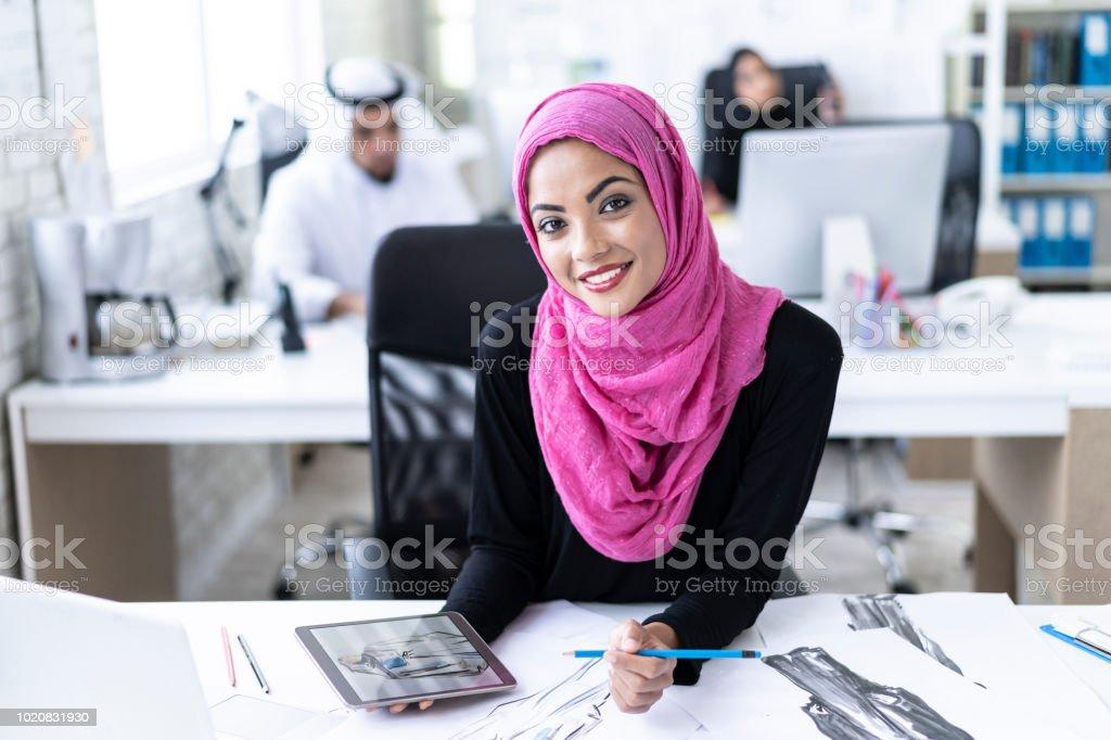 Beautiful arab woman creating fashion models in studio, using tablet...