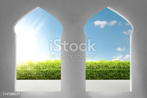 Beautiful arches of mosque with garden views and sunlight rays over blue sky background