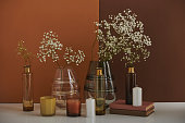 istock Beautiful aromatic still life composition with flowers in glass vessels and perfume candles on brown background 1293647418
