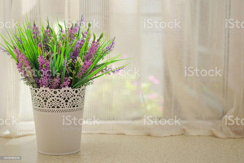 Beautiful artificial flowers with lavender on the window stock photo