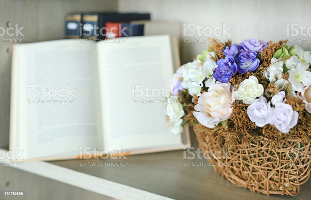 Beautiful Artificial Rose Flower In Basket On The Bookshelf Library Against Blur Of Open Hardcover