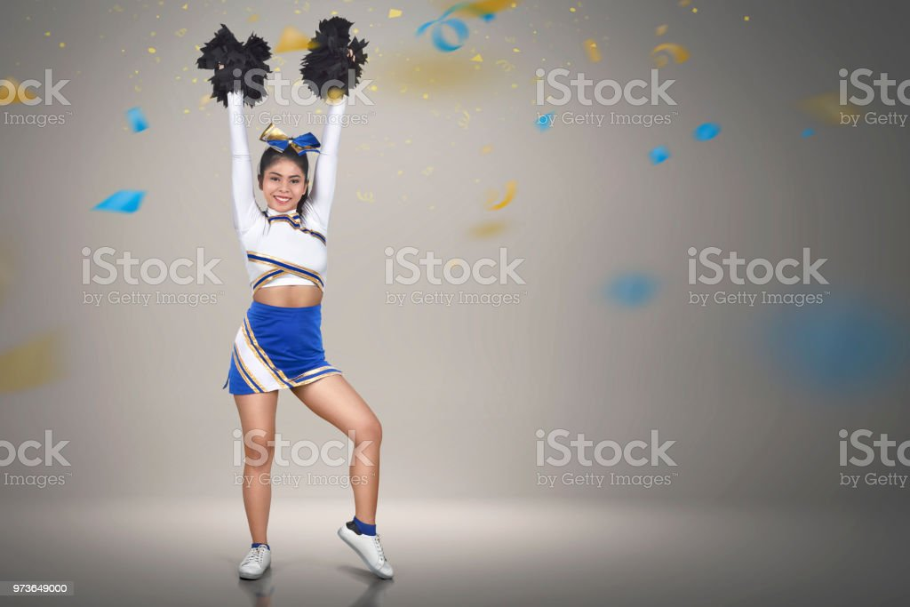 Beautiful asian cheerleader action with pom-poms stock photo