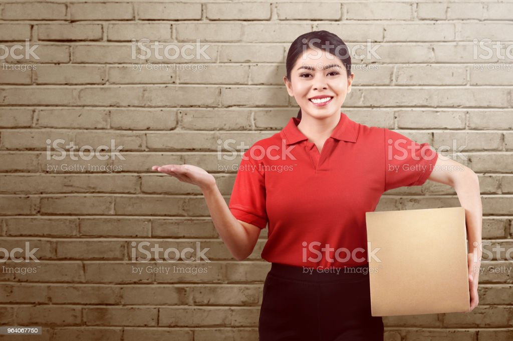 Beautiful asian delivery woman holding parcel and showing something - Royalty-free Adult Stock Photo