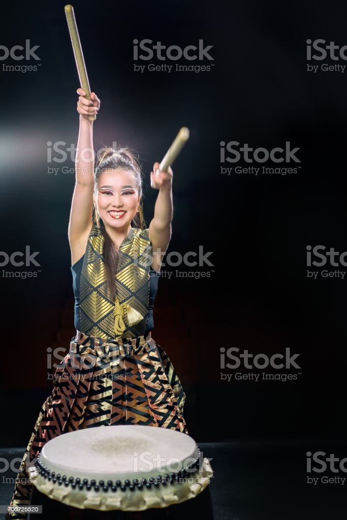 beautiful asian drummer girl with drumsticks, studio shot on a dark background. copy space. stock photo