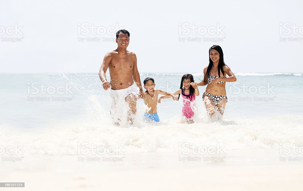 Beautiful Asian family coming out of the water stock photo