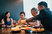istock Beautiful asian family enjoying a meal in a restaurant 1268557783