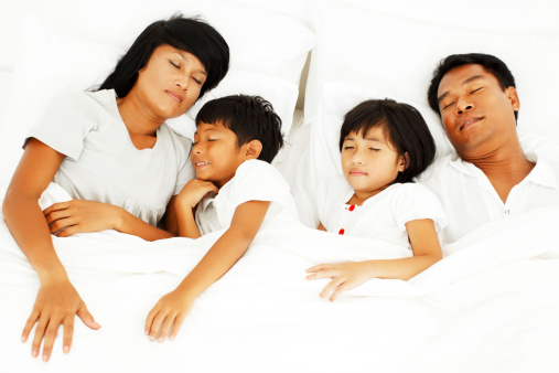 Above view of Asian family sleeping in their bed.