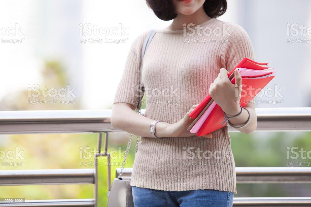 Hermosa asiática femenino estudiante sosteniendo sus libros sonriendo felizmente permanente al aire libre, Educación de gente aprendiendo el concepto de inteligente adolescente de escuela secundaria programa - Foto de stock de Adolescente libre de derechos