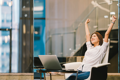 istock Beautiful Asian girl celebrate with laptop, hands stretch or finish work success pose, education or technology or startup business concept, modern office or living room with copy space 691886246