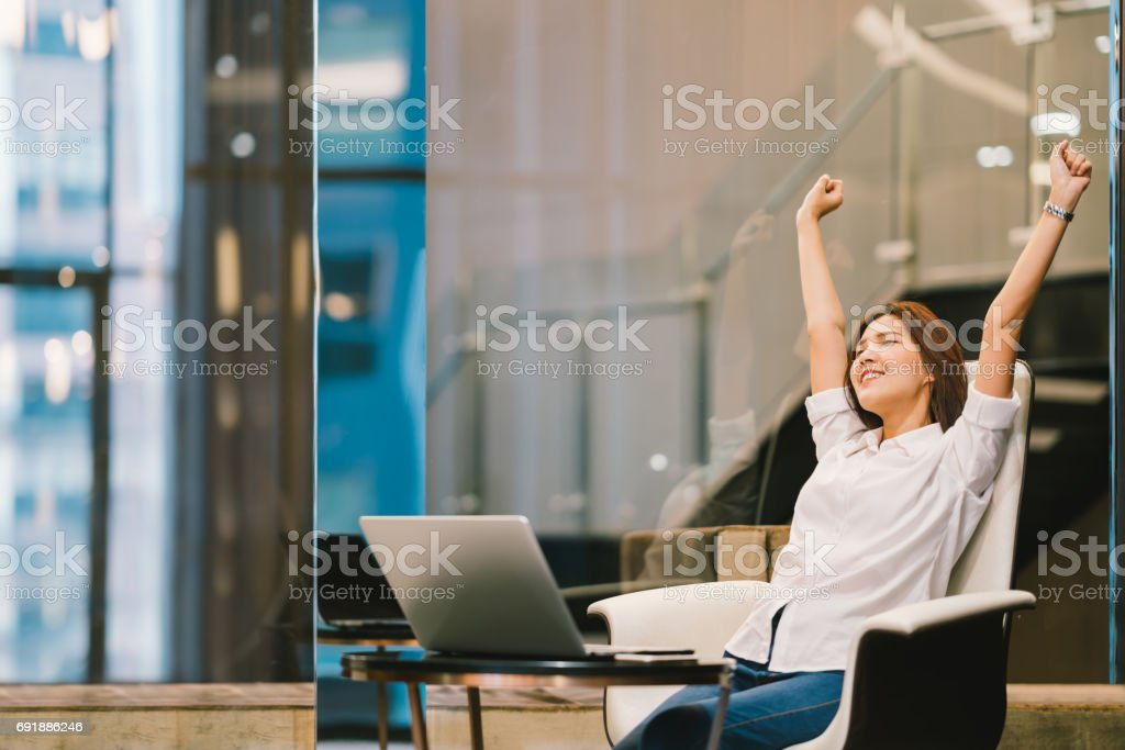 Beautiful Asian girl celebrate with laptop, hands stretch or finish work success pose, education or technology or startup business concept, modern office or living room with copy space stock photo