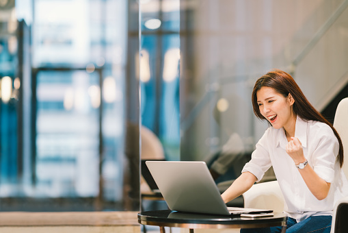 istock Beautiful Asian girl celebrate with laptop, success or happy pose, education or technology or startup business concept, modern office or living room with copy space 686380490