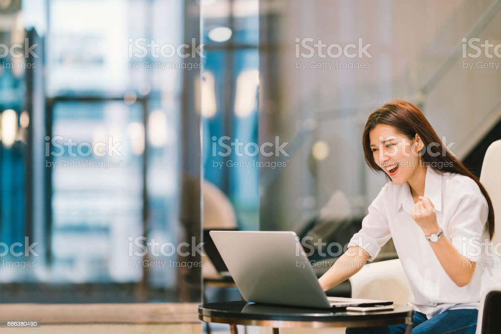 Beautiful Asian girl celebrate with laptop, success or happy pose, education or technology or startup business concept, modern office or living room with copy space stock photo