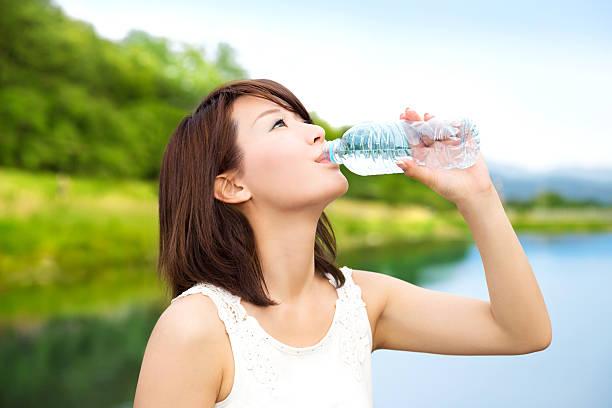 美しいアジアの女の子を飲みながら、自然のミネラルウォーター ストックフォト