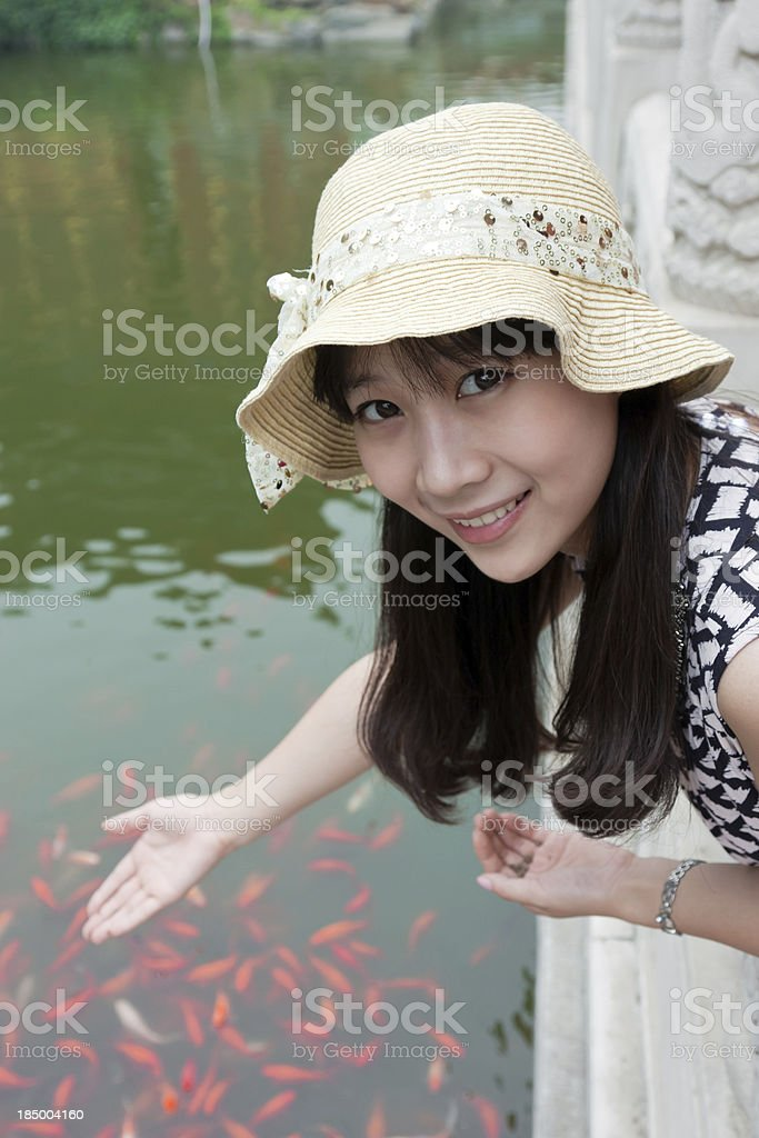 Beautiful oriental girl feeding goldfish royalty-free stock photo