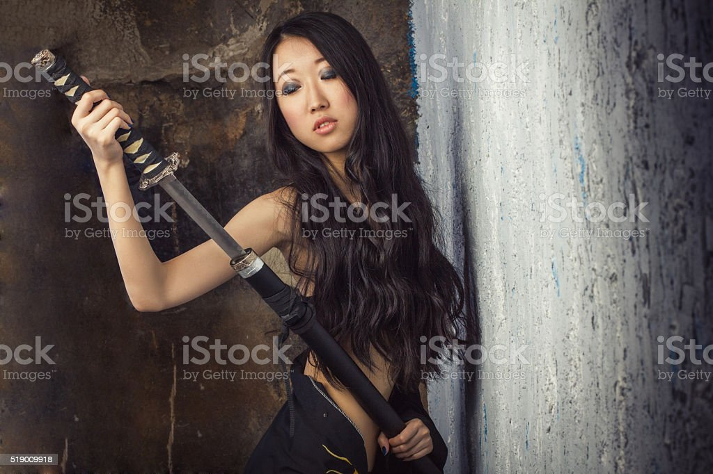 beautiful Asian girl in kimono with a katana stock photo