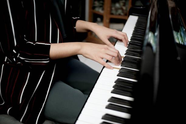 Beautiful asian girl learn to play piano. stock photo