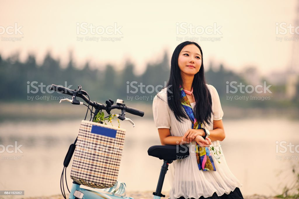 Beautiful Asian Girl  On A Bike by the river foto stock royalty-free