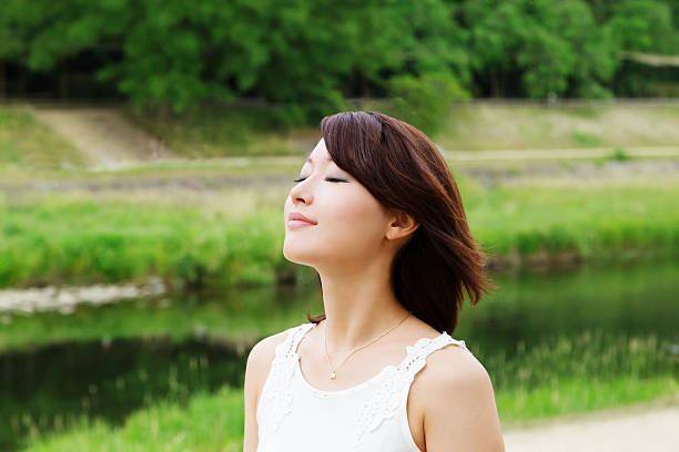 Beautiful Asian girl relaxing in green with a smile on her lips. Breathing deeply and relaxing image.  spring flowing water stock pictures, royalty-free photos & images