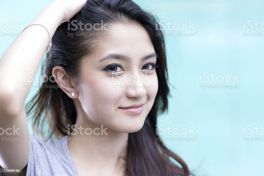 Beautiful asian girl running her hand through her hair stock photo